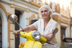 A senhora toca no scooter& x27; volante de s foto de stock royalty free