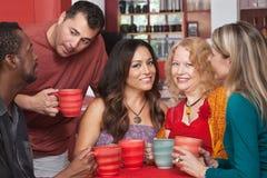 Senhoras atrativas com os homens no café Foto de Stock