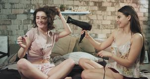 Senhoras atrativas na manhã usando um hairdryer para obter mais consideravelmente, vestindo um assento dos pijamas na cama vídeos de arquivo