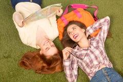 Senhoras bonitas do turista que encontram-se na grama verde Foto de Stock