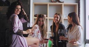 Senhoras bonitas que olham em linha reta à câmera e que sorriem consideravelmente ao guardar vidros do vinho em pijamas à moda vídeos de arquivo