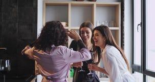 Senhoras carismáticas que dançam em um whit à moda dos pijamas vidros de vinho em um projeto urbano moderno do estúdio eles senti vídeos de arquivo