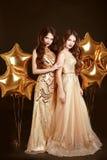 Senhoras elegantes no partido Meninas 'sexy' bonitas que vestem no fá do ouro Fotografia de Stock Royalty Free