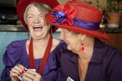 Senhoras que desgastam cartões de jogo vermelhos dos chapéus Fotografia de Stock