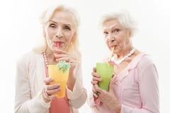 Senhoras superiores alegres que apreciam a bebida exótica Foto de Stock Royalty Free