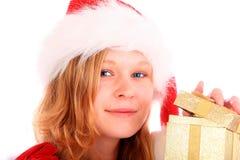 A senhorita Santa está abrindo uma caixa de presente dourada Imagens de Stock