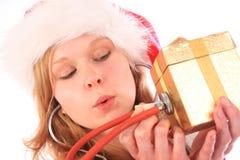 A senhorita Santa está soando uma caixa de presente dourada Foto de Stock