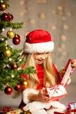 Senhorita Santa que abre um presente Fotografia de Stock Royalty Free