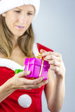 Senhorita Santa que oppening um presente Fotos de Stock Royalty Free