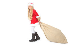 Senhorita Santa que puxa o saco pesado de Papai Noel Fotografia de Stock Royalty Free