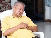 Seniele Aziatische mensen die op een stoel bij woonkamer met hartaanvallen zitten Beide oude mensen` s handen op borst wegens har stock fotografie