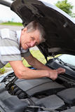 Seniior driver examining car engine Stock Image