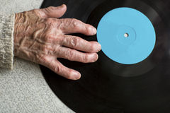Senile hand is on vinyl LP. Close-up of the old man or old woman hand. Stock Images