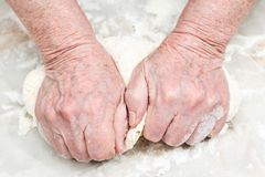 Senile hands knead the dough. Female senile hands knead the dough on a table, close-up Stock Image