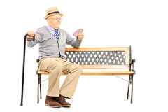 Senile old man with cane, on bench imagining playing cards with Stock Images