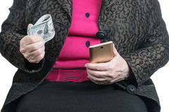 Senile woman hands with money and smartphone Royalty Free Stock Image