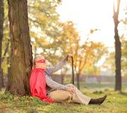 Seniler alter Mann, der draußen in einem Superheldkostüm sitzt Stockfoto