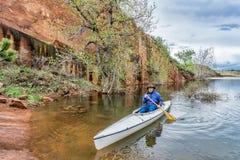 Senio canoe paddler near sandstone cliff Royalty Free Stock Image