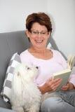 Senio woman reading in sofa Stock Photos