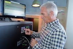 Senion man doing tv installation. Senion man doing a tv installation Royalty Free Stock Photos