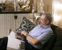 Senion man reading sofa luxury living room. Black and silver Stock Photos