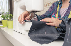 Senion seamstress woman working on sewing machine. Senior seamstress woman working with clothing item on a sewing machine Royalty Free Stock Photography