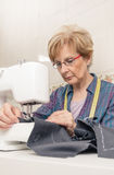 Senion seamstress woman working on sewing machine. Senior seamstress woman working with clothing item on a sewing machine Royalty Free Stock Photo