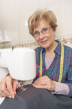 Senion seamstress woman working on sewing machine Royalty Free Stock Photo