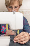 Senion seamstress woman working on sewing machine Stock Photos
