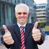 Senior. Happy senior business man holding his thumbs up outside the office stock images