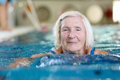 Senior active lady swims in the pool Royalty Free Stock Photos
