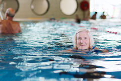 Senior active lady swims in the pool. Happy healthy senior woman enjoying active lifestyle swimming in the pool stock photography