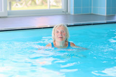 Senior active lady swims in the pool Royalty Free Stock Photography