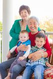 Senior Adult Chinese Couple Sitting With Their Mixed Race Grandchildren royalty free stock photo
