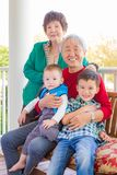 Senior Adult Chinese Couple Sitting With Their Mixed Race Grandchildren. Senior Adult Chinese Couple Sitting With Their Two Mixed Race Grandchildren royalty free stock photos