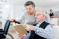 Senior adult couple checking brochure at home. Senior adult couple checking a brochure at home stock image