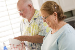 Senior Adult Couple Washing Dishes Together Inside Kitchen Stock Images