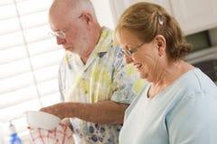Senior Adult Couple Washing Dishes Together Inside Kitchen Stock Images
