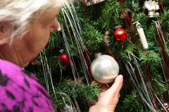 Senior adult decorate a christams tree Royalty Free Stock Image