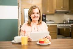 Senior adult having breakfast holding a tablet Royalty Free Stock Image