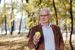 Senior adult holding green apple Royalty Free Stock Images