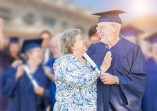 Senior Adult Male In Cap and Gown Being Congratulated By Wife At Royalty Free Stock Photo