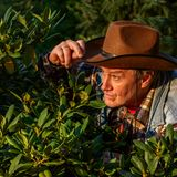 Senior adult man or a farmer, in a brown cowboy hat, looks out o royalty free stock photography