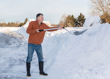 Senior adult man finishes digging out drive in snow Stock Photos