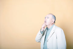 Senior adult man with his hand on his chin looking up inquisitively Stock Image