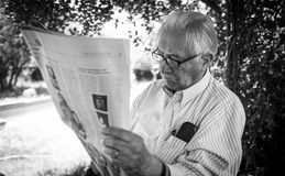 Senior man. Senior adult man reading newspaper in the garden Stock Photos