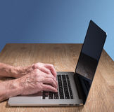 Senior adult man touch types on laptop. Senior caucasian adult man types on modern keyboard of laptop or ultrabook on wooden desk with copy space Stock Image