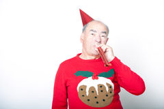 Senior adult man wearing Christmas jumper blowing party blower Stock Images