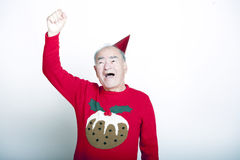 Senior adult man wearing Christmas jumper raising his arm in the air Stock Image