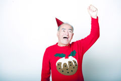 Senior adult man wearing Christmas jumper raising his arm in the air Stock Photos